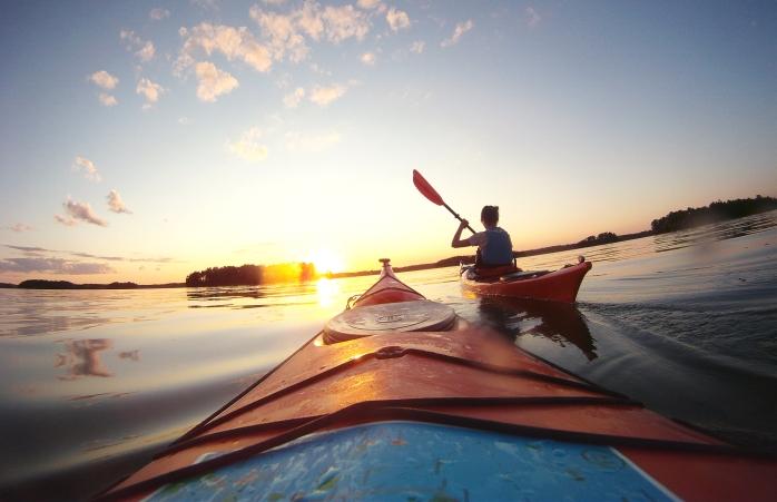 A couple kayak through Finland's lakes.