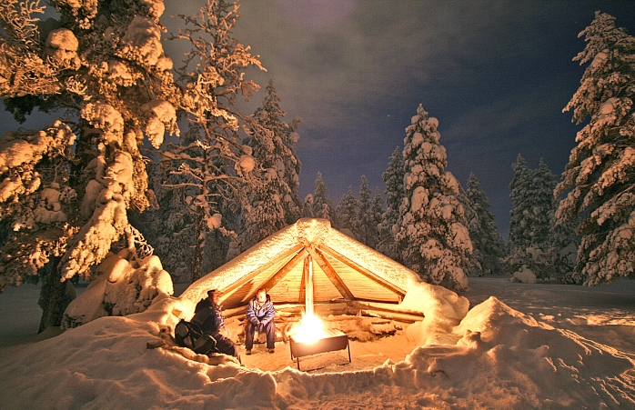 Two guys warm by the fire in the forest during winter in Finland.