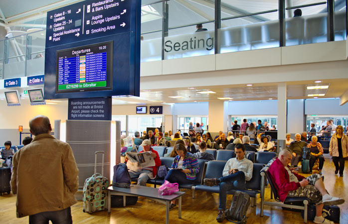 A man checks the departure screen to find his gate - Bristol Airport, UK