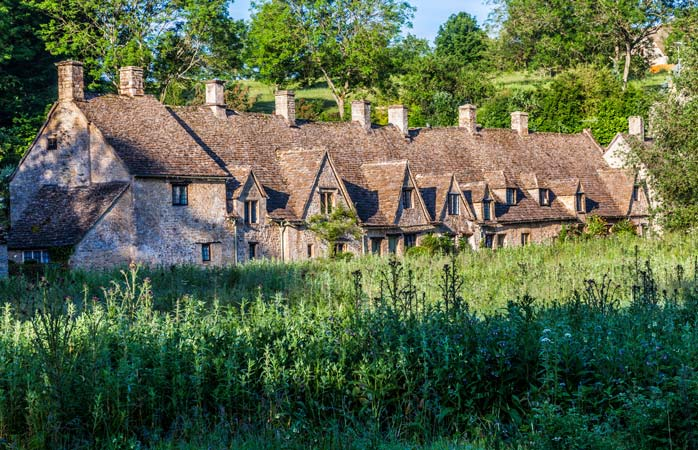 Sun gleaming over the famous cottages of Arlington Row in the Cotswolds