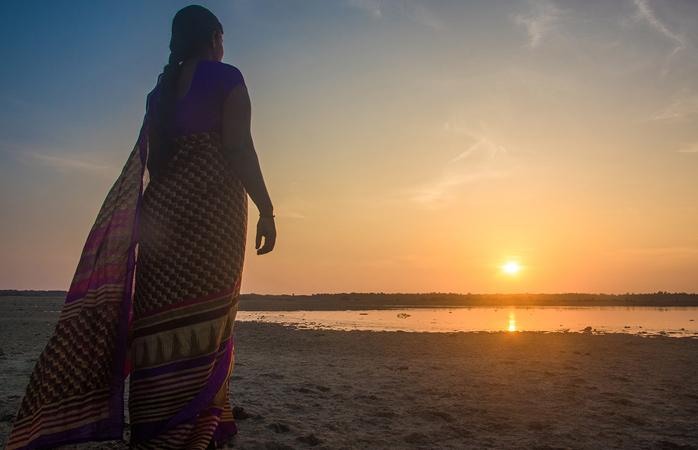 Woman in sari looking at the rising sun