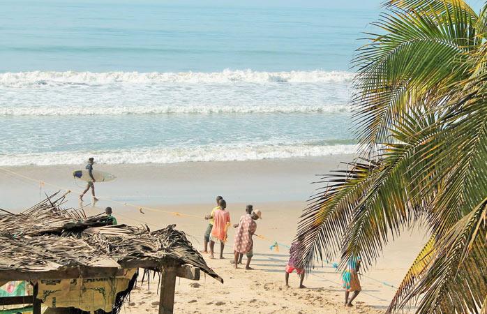 A surfer among fishermen in Konkrobite – a typical scene along Ghana's coastline