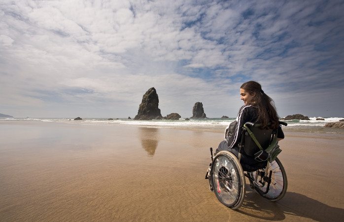 Young woman in a wheel chair visiting Canon Beach in Oregon, USA.
