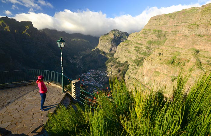 A woman admires the view of Madeira Island from a viewpoint